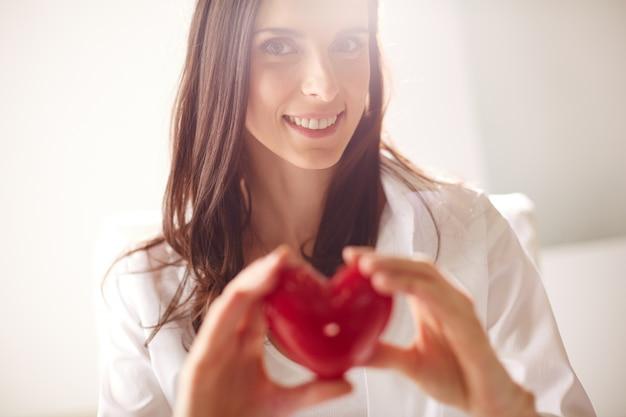 Mulher romântica que mostra um coração
