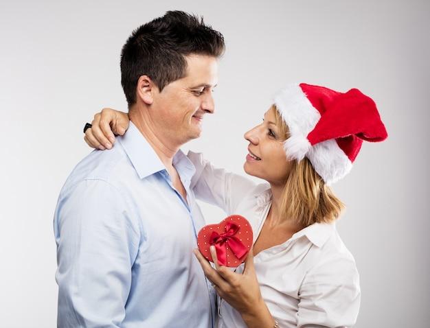 Mulher romântica que prende um presente ao lado do marido