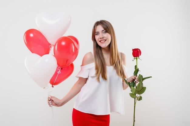 Mulher romântica wirh rosa vermelha e balões em forma de coração isolados