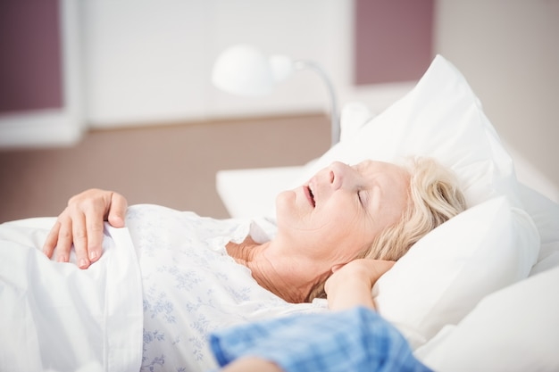 Mulher roncando na cama ao lado do marido