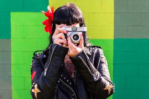 Mulher roqueira tatuada na jaqueta de couro e flor no cabelo na parede verde, tirando uma foto com uma câmera vintage.