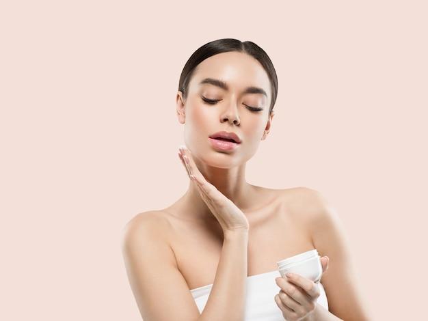 Mulher rosto creme cosmético cuidados com a pele saudável retrato de beleza isolado no branco cor de fundo rosa
