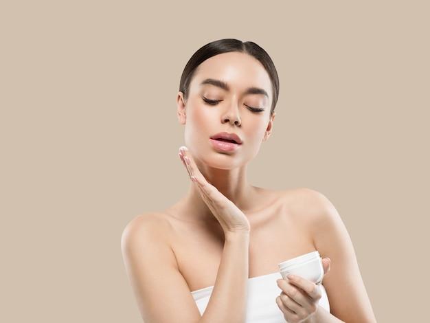 Mulher rosto creme cosmético pele saudável cuidados beleza retrato isolado no branco cor de fundo marrom