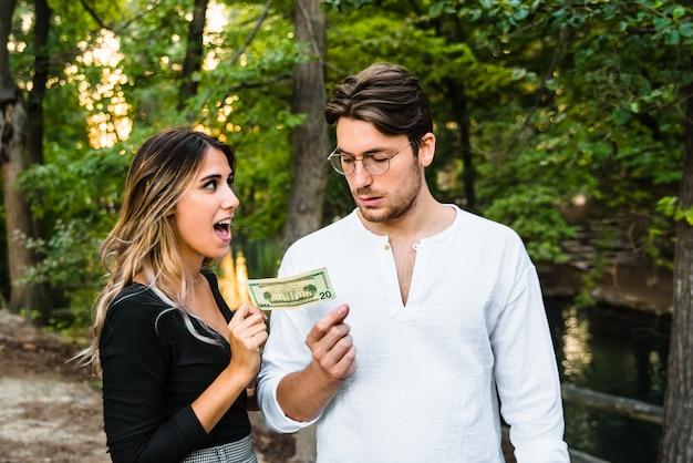 Mulher rouba uma nota de dólar da mão de um homem.