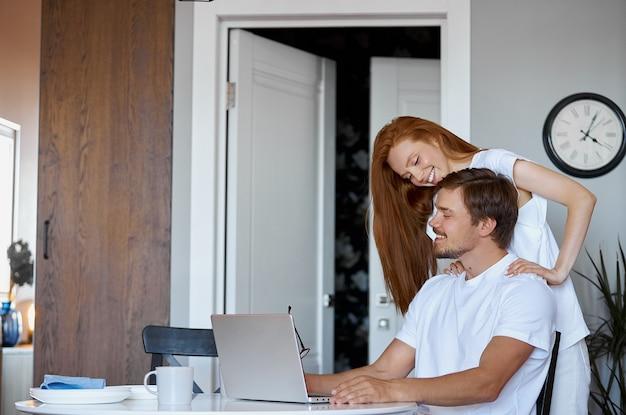 Mulher ruiva adorável apoiando marido que trabalha