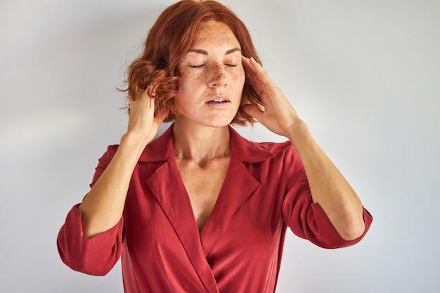 Mulher ruiva ajeitando o cabelo isolado em um estúdio em fundo branco