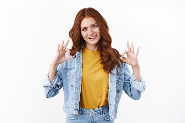 Mulher ruiva alegre, ambiciosa e autoconfiante em jaqueta jeans aprovar boa ideia, mostrar satisfatória ok, ok sinalizar e sorrir, acenar concordando, garantir tudo perfeito, parede branca