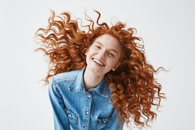 Mulher ruiva alegre com cabelo encaracolado a sorrir, rindo.