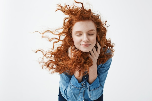 Mulher ruiva alegre com cabelo encaracolado a voar sorrindo rindo com os olhos fechados.