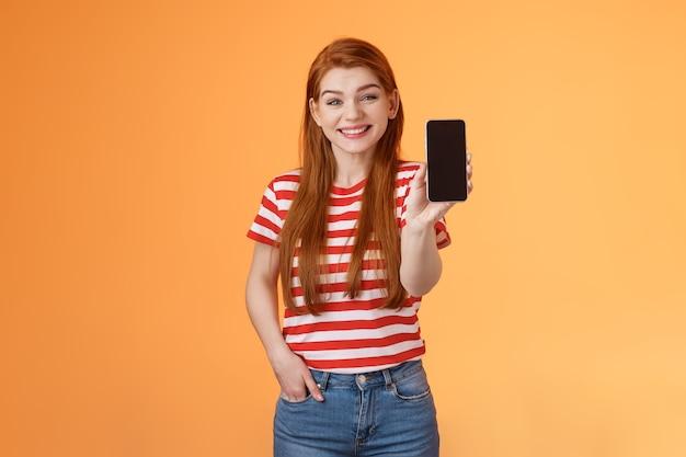 Mulher ruiva alegre de boa aparência apresenta produto de recurso de mídia social espera câmera de exibição de smartphone ...