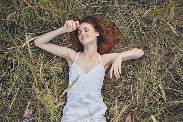 Mulher ruiva alegre em um vestido branco deitada na grama descansar ao ar livre