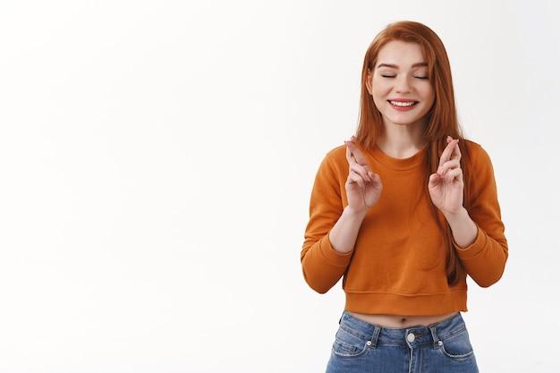 Mulher ruiva alegre esperançosa mulher urbana corte de cabelo vermelho fechar olhos sorrindo alegremente cruzar os dedos boa sorte fielmente aguardando o desejo em realidade antecipando a parede branca