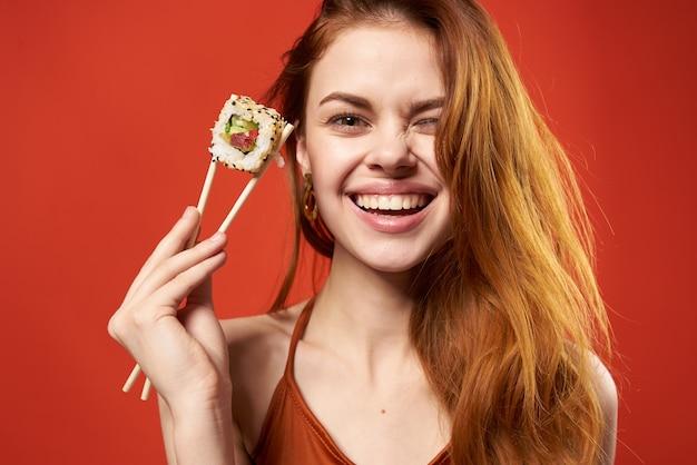 Mulher ruiva alegre rola de sushi dieta divertida close-up