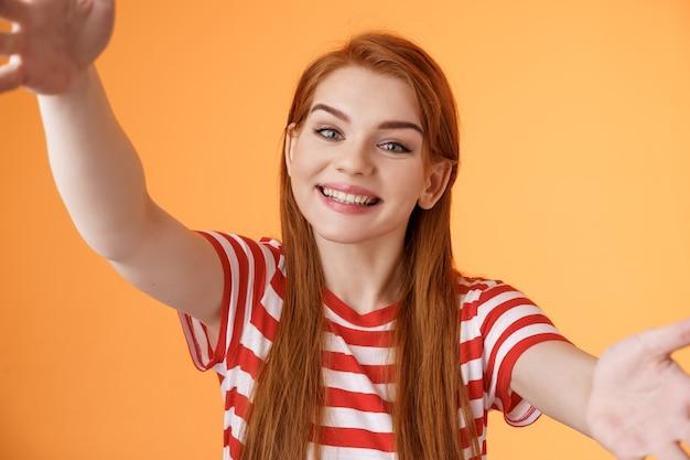 Mulher ruiva amigável e alegre dos anos 20 estende os braços, segura a câmera com as duas mãos tirando uma selfie, inclina a cabeça fofa, grave videoblog novo gadget, alegra-se, fique com o fundo laranja, mostre um sorriso adorável