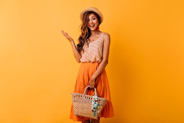Mulher ruiva animada com chapéu, segurando um saco de palha. garota de cabelos compridos em êxtase com roupa de verão, aproveitando o bom dia.