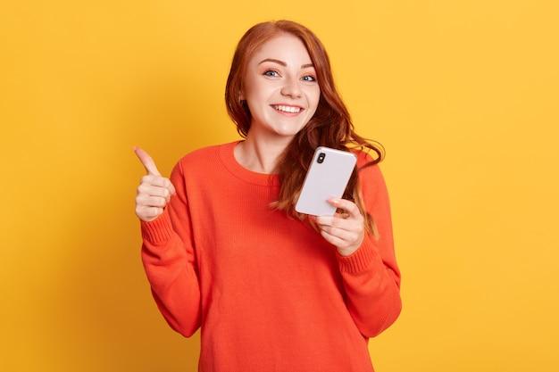 Mulher ruiva animada com suéter laranja posando contra uma parede amarela, segurando um telefone inteligente moderno nas mãos e mostrando o polegar
