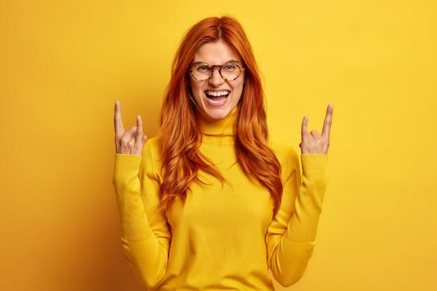 Mulher ruiva animada e alegre mostra gesto de rock n roll faz chifres com os dedos, ri, gosta de ouvir música rock favorita usa blusa de gola alta casual.