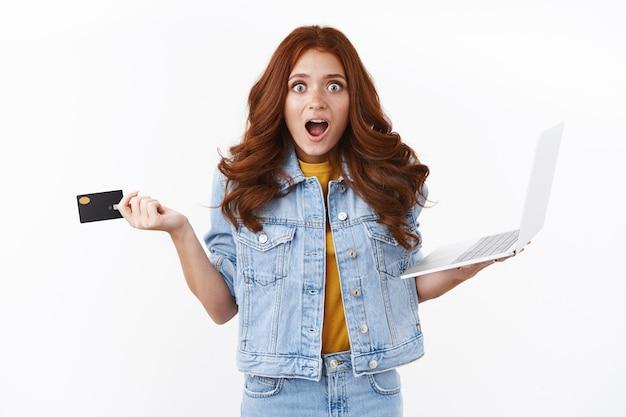 Mulher ruiva animada e fofa surpresa em jaqueta jeans, parece entusiasmada e divertida enquanto faz compras online, segura o laptop para aumentar o cartão de crédito em espanto, ofegante e maravilhada com as promoções legais da internet