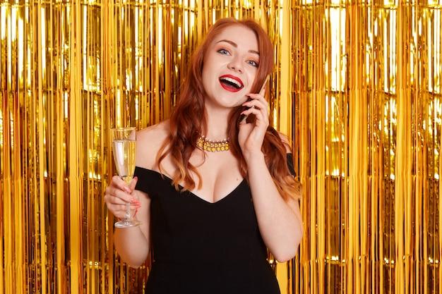 Mulher ruiva animada falando ao telefone com uma taça de vinho, comemorando seu aniversário, usando um vestido preto e posando com a boca aberta
