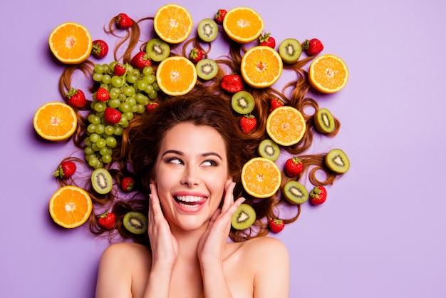 Mulher ruiva artística posando com frutas no cabelo
