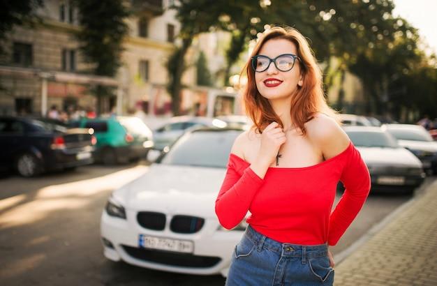 Mulher ruiva atraente de óculos, vestindo blusa vermelha