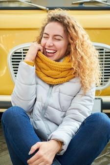 Mulher ruiva atraente engraçada e cacheada sentada na frente de um carro amarelo e sorrindo com os olhos fechados