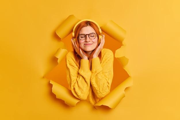 Mulher ruiva atraente, melomana fecha os olhos de alegria, desfruta de uma melodia agradável, ouve música favorita através dos fones de ouvido, usa um casaco casual amarelo