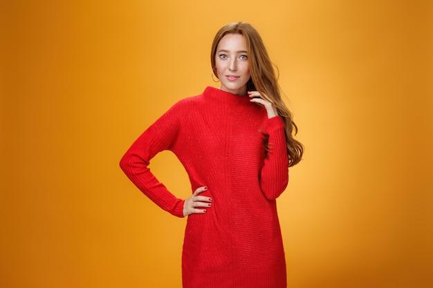 Mulher ruiva atraente, sensual e romântica em um elegante vestido de malha vermelha segurando a mão no quadril, sorrindo misteriosamente enquanto flertando, brincando com o cabelo olhando para a câmera sobre fundo laranja