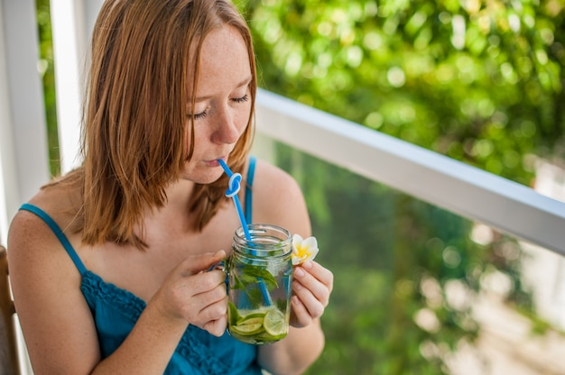 Mulher ruiva bebendo um mojito no terraço