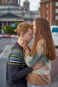Mulher ruiva beija um homem no topo da cabeça, uma mulher com longos cabelos escuros e grossos no suéter