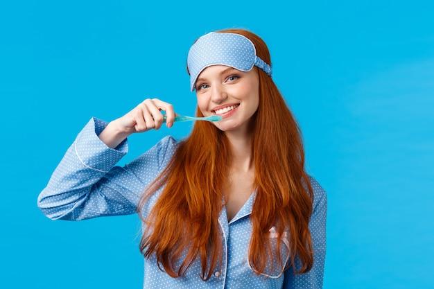 Mulher ruiva bonita alegre em roupa de dormir, pijama e máscara de dormir, escovar os dentes segurando a escova de dentes e sorrindo alegre, acordar e cuidar da higiene, parede azul em pé