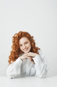 Mulher ruiva bonita com cabelos cacheados, sorrindo, olhando para a câmera, sentado à mesa sobre parede branca