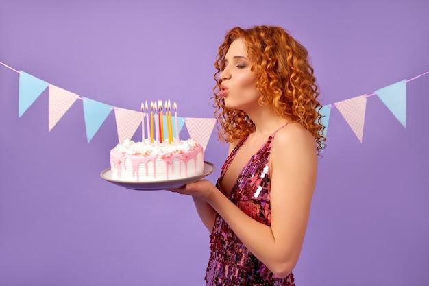 Mulher ruiva bonita com cachos em um vestido brilhante segura um bolo e apaga as velas isoladas no roxo