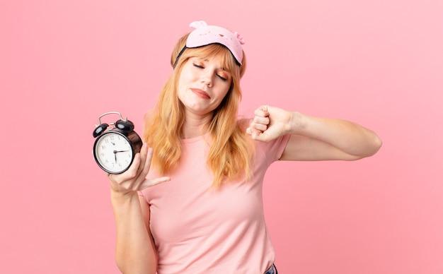 Mulher ruiva bonita de pijama e segurando um despertador. conceito de acordar