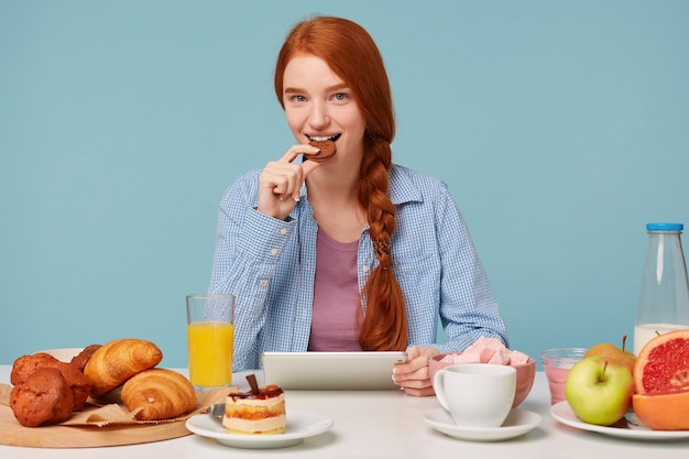 Mulher ruiva bonita e atraente com um sorriso, comendo biscoitos sentado à mesa