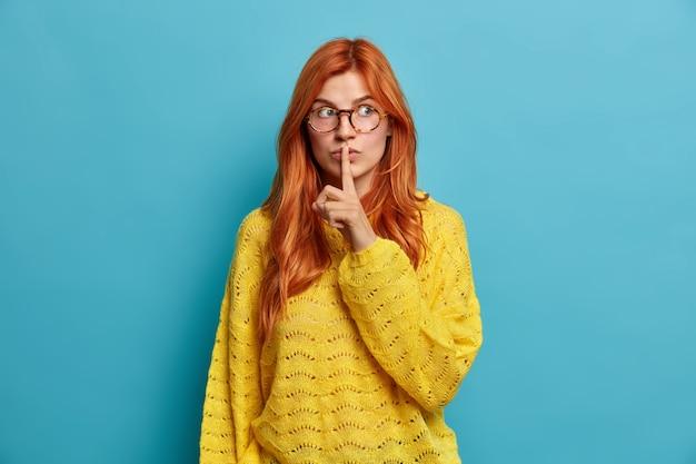 Mulher ruiva bonita e atraente faz gesto de silêncio, mantém o dedo indicador nos lábios, faz sinal de silêncio, usa óculos ópticos e suéter amarelo.