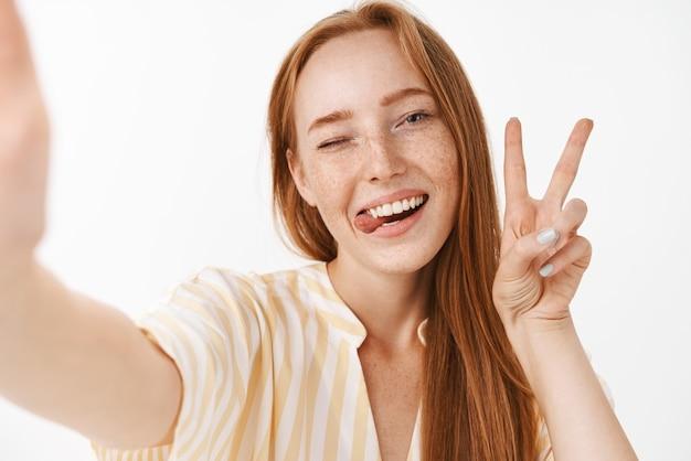 Mulher ruiva bonita e elegante com sardas fofas, mostrando a língua e sorrindo de alegria, piscando alegremente, mostrando o sinal da paz, tirando selfie no smartphone