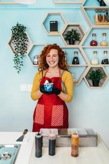 Mulher ruiva bonita e positiva ruiva sorrindo e trabalhando em uma loja de sorvetes artesanais. ela está preparando e servindo uma deliciosa comida doce.