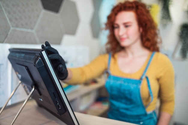 Mulher ruiva bonita e positiva ruiva sorrindo e trabalhando em uma loja de sorvetes artesanais. ela está recebendo pedidos de novos clientes.