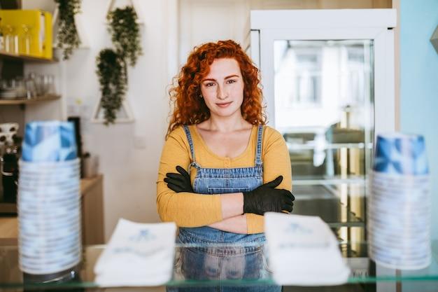 Mulher ruiva bonita e positiva ruiva sorrindo e trabalhando em uma loja de sorvetes artesanais.