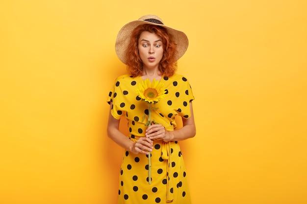 Mulher ruiva bonita e surpresa posando em um vestido polca amarelo e chapéu de palha