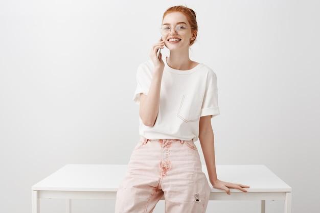 Mulher ruiva bonita elegante falando ao telefone, inclinada sobre a mesa do escritório