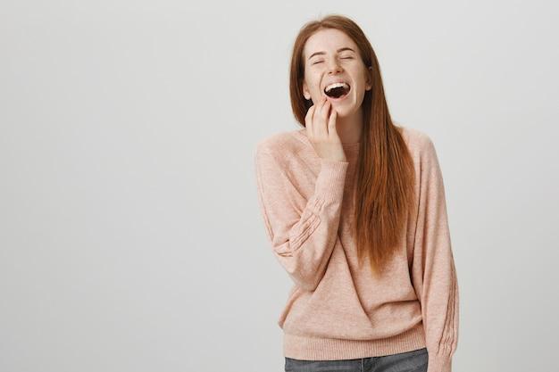 Mulher ruiva bonita feliz rindo, assistindo comédia