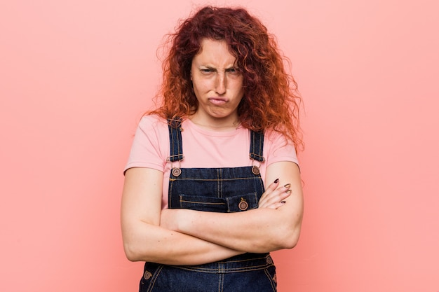 Mulher ruiva bonita jovem ruiva vestindo um jeans dungaree carrancuda rosto em descontentamento, mantém os braços cruzados.