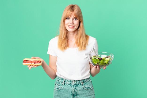 Mulher ruiva bonita segurando uma salada e um cachorro-quente. conceito de dieta