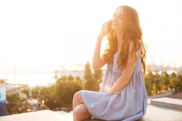 Mulher ruiva bonita sorridente com cabelos longos, falando no telefone
