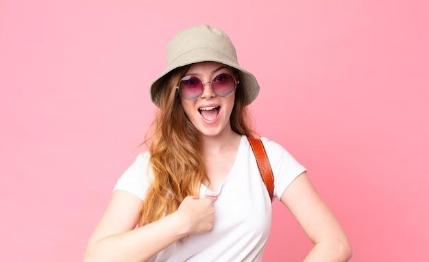 Mulher ruiva bonita turista chocada e surpresa com a boca aberta, apontando para si mesma
