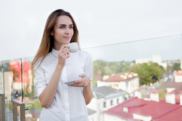 Mulher ruiva branca na camisa branca, bebendo café