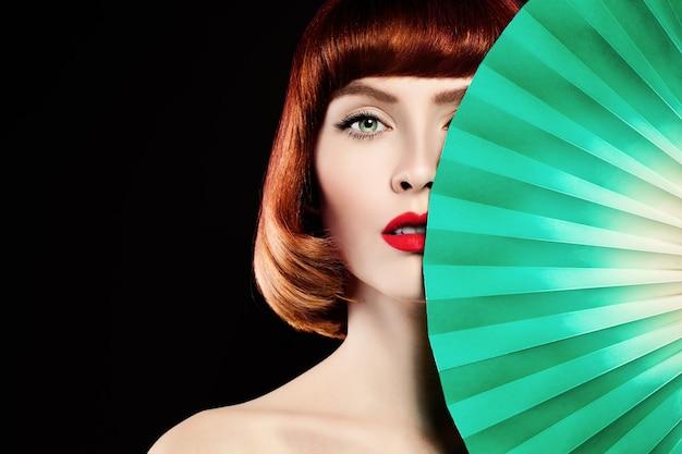 Mulher ruiva. cabelo com coloração vermelha, lábios vermelhos e fundo de papel verde
