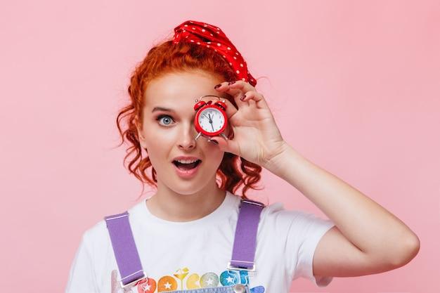 Mulher ruiva cacheada com olhos azuis olhando para a frente e segurando um despertador vermelho na parede rosa